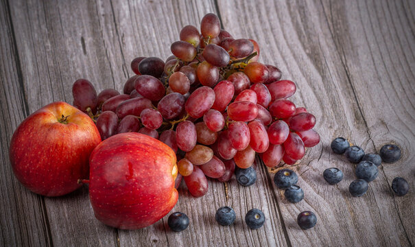red grapes and apples on dark wood background