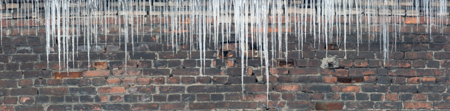large group of icicles on brick wall background