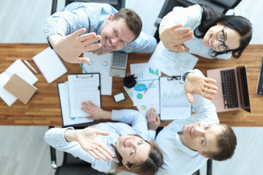 Group of business people sitting at table and waving their hands top view
