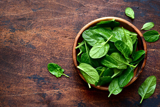 Fresh organic spinach leaves in a wooden bowl . Top view with copy space.