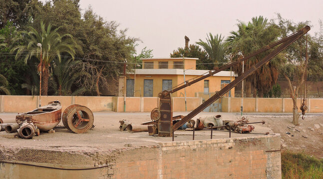 A traditional Egyptian house, a palm garden, a simple crane, an old boat and other objects.