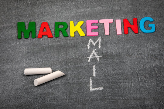 Email Marketing concept. Colored letters of the alphabet on a dark chalk board.