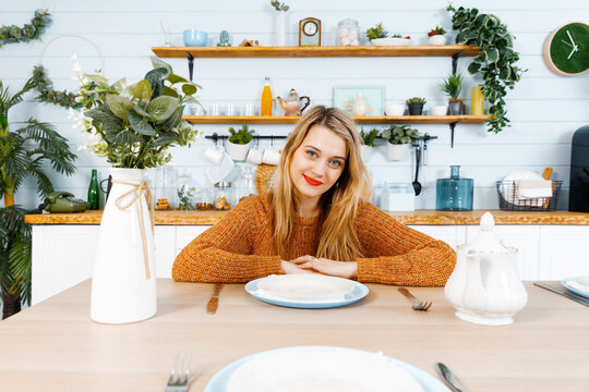 Young woman sitting at the kitchen table in front of an empty plate and looks directly in the camera.