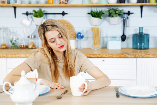 Young woman sits at the kitchen table with mug on her hand. Blurred background.