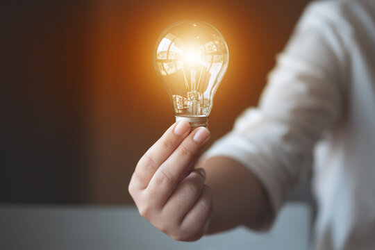 ideas creativity concept, woman holding light bulb in office..