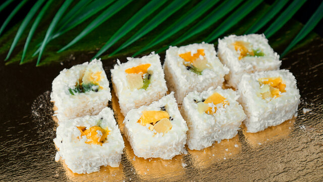 Dessert Sushi - Roll with Various Fruit and Cream Cheese inside. On a gold background and with a tropical leaf
