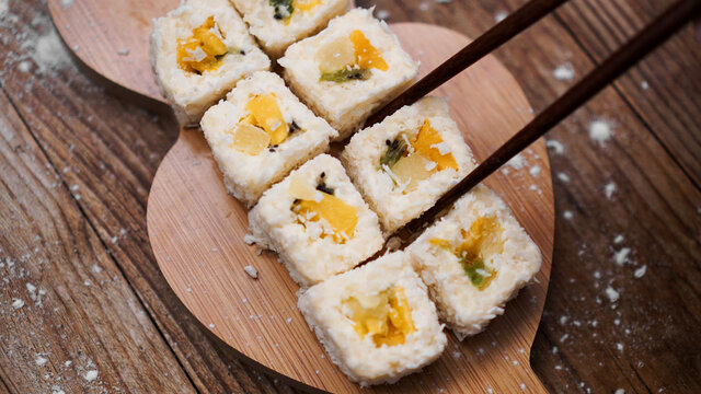 Sushi delivery. Sweet rolls made from rice, pineapple, kiwi and mango. Rolls on a wooden background. Wooden sticks for sushi.
