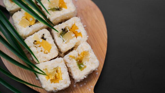 Dessert sushi. Sweet kiwi, pineapple and banana sushi rolls. Sushi on a wooden tray on a black background
