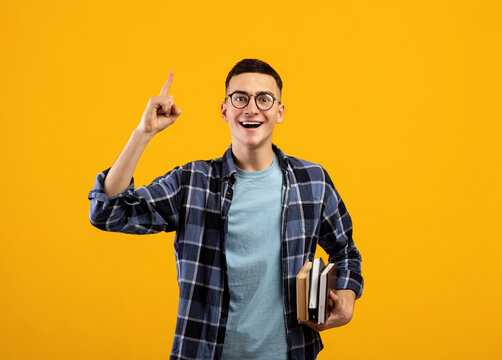 Millennial student with books having creative idea, showing eureka gesture, experiencing AHA moment on orange background