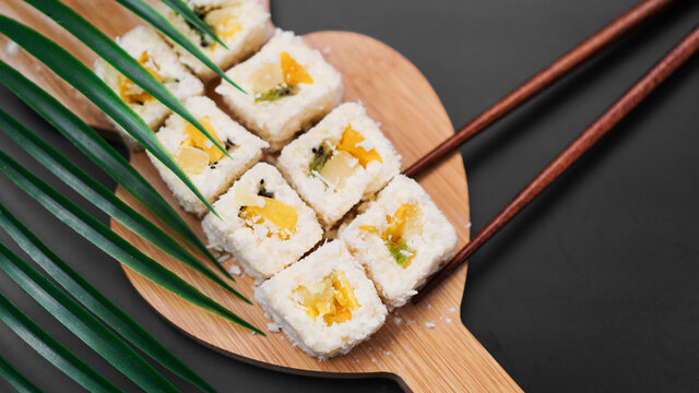 Dessert sushi. Sweet kiwi, pineapple sushi rolls. Sushi on a wooden tray on a black background. Holding a sweet roll with wooden sticks.