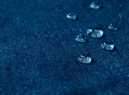 Water drops on blue waterproof fabric.