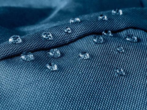 Water drops on waterproof membrane fabric. Detail view of texture of blue waterproof cloth.