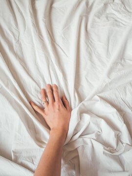 Woman's hand on background of crumpled bed sheet. Creased white linen. Woman touches unmade bed. Cozy imperfect house. Non-ideal cozy home.