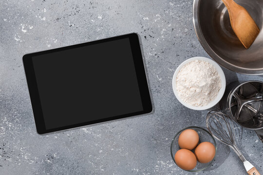 Ingredients, tools for baking and tablet with blank screen and place for text or image on gray table. recipe, cookbook, cooking courses online template