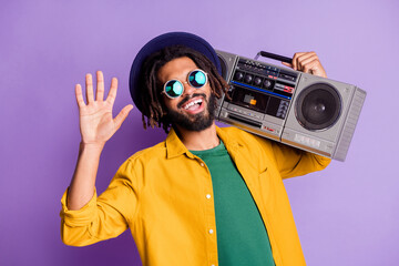 Photo of cheerful carefree dark skin man carry boom box arm palm wave isolated on violet color background