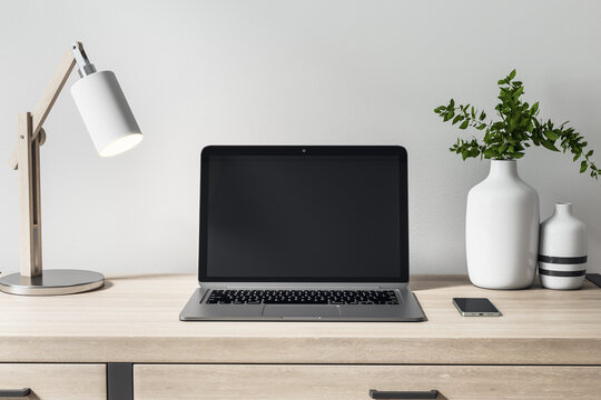 Blank black laptop monitor on wooden table with decor elements for comfortable remote work. Mockup