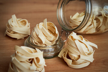 Close up of jar of scattered tagliatelle on a kitchen counter