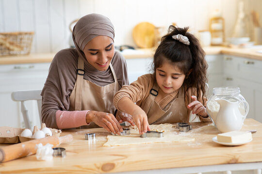 Pretty Young Muslim Lady Making Cookies With Her Little Daughter In Kitchen