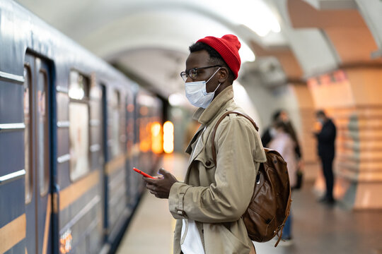 Black millennial man in trench coat, red hat wearing face mask as protection against covid-19, flu virus, waiting for the train at subway station, using cellphone. New normal, pandemic concept.