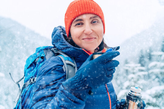 Middle-aged woman smiling, looking at camera drinking a hot drink from thermos flask dressed warm down jacket while she trekking winter mountains route. Active people in the nature concept image.
