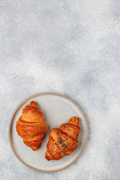 Freshly baked homemade croissants for breakfast. Traditional and whole-grain croissant with pumpkin seeds in a gray plate on a concrete or stone background. Selective focus, copy space