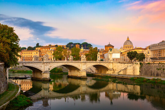 Cityscape view of Rome at colorful sunset with Ponte Sant Angelo and St Peter Cathedral in Vatican.