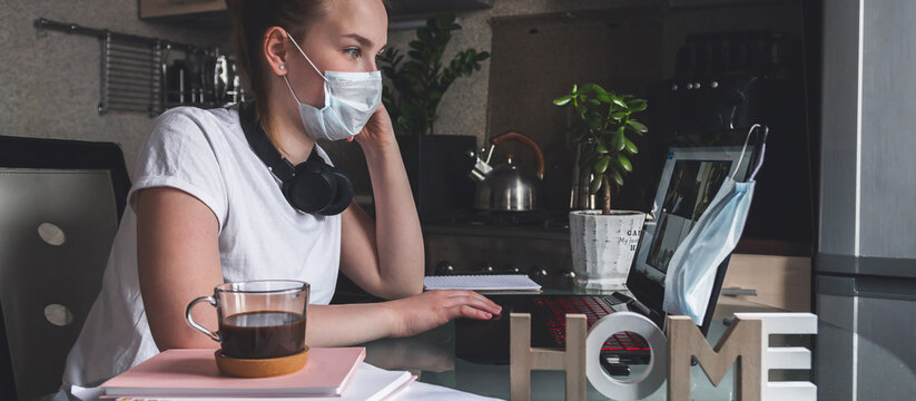 Coronavirus. Quarantine. Online training, remote work, office at home in the kitchen. Remote work, training, education. The girl is studying, working remotely. Coronavirus pandemic in the world.