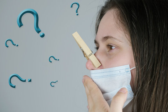 young woman, girl in a white medical mask with long blond hair, her nose is clamped with a wooden clothespin, questions, concept stinks, loss of smell due to coronavirus, flu