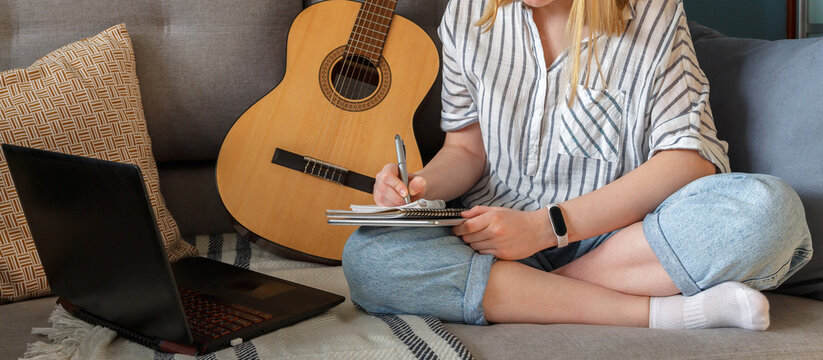 Online music learning. Girl playing acoustic guitar and watching online course on laptop while lesson at home. Online training, online classes. Remote training.Online education