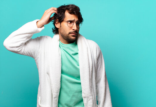 young handsome indian man feeling puzzled and confused, scratching head and looking to the side and wearing bath robe