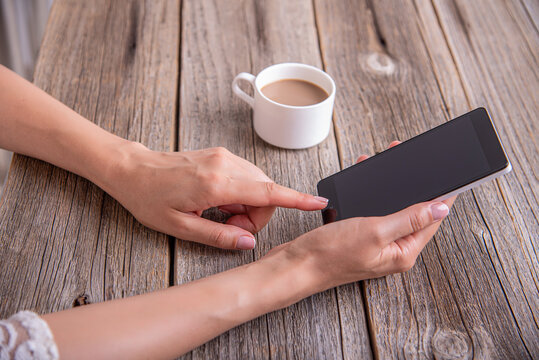 Smartphone in female hands on the background of a wooden table and a cup of coffee.