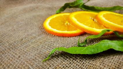 Świeży, soczysty plasterek pomarańczy i zielony liść.