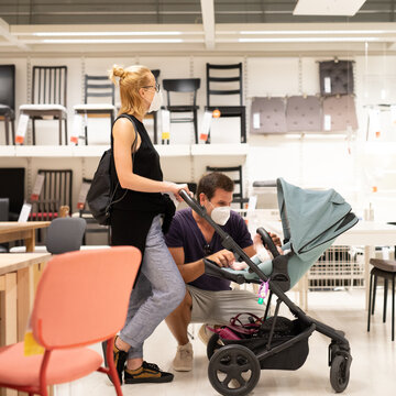 Young family with newborn in stroller shopping at retail furniture and home accessories store wearing protective medical face mask to prevent spreading of corona virus when shops reopen.