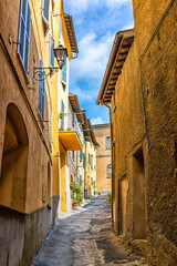 Chiusi, Italy dark narrow street alley in small historic medieval town village in Tuscany vertical view during day with orange yellow bright vibrant