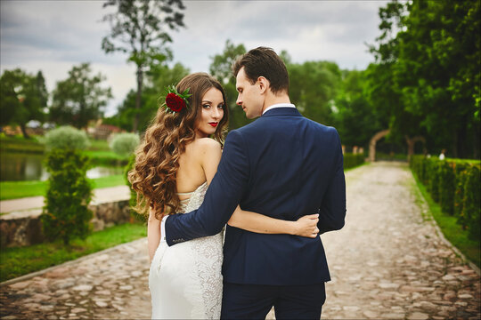 Beautiful young bride with wedding hairstyle decorated with flowers hugs with her handsome groom