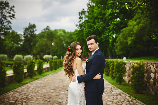 Stylish couple of happy newlyweds posing in the park after the wedding ceremony on their wedding day. Perfect couple, bride and groom posing outdoors
