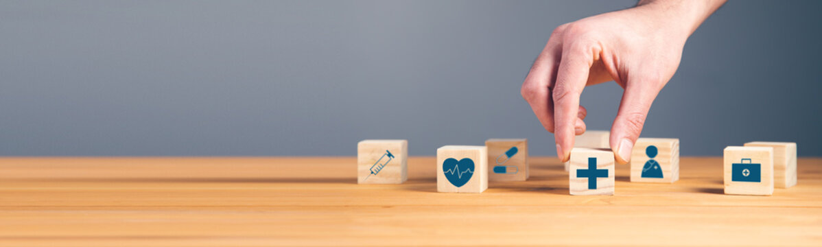 man holding wooden blocks with medical symbol