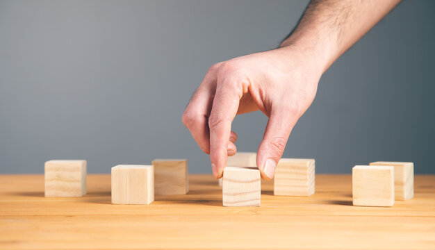 Hand holding wooden block cubes