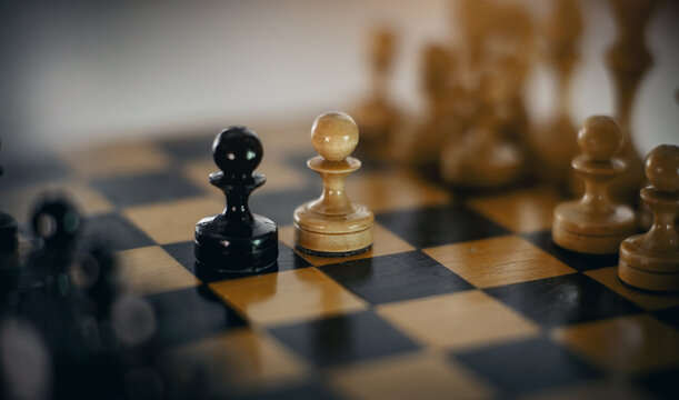 Two chess pieces are pawns: black and white. Wooden chess pieces on the chessboard.