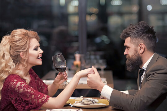 Young couple at restaurant having dinner. Man and woman rest in restaurant. People drink in club. Lovers sit in cafe bar, date meeting in pub.
