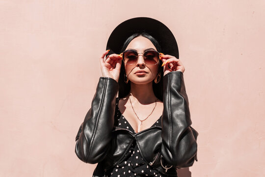 European fashionable woman puts on sunglasses near pink wall on sunny day. Beautiful girl in fashionable summer black clothes in elegant stylish hat poses near building. Sun rays and beauty lady.