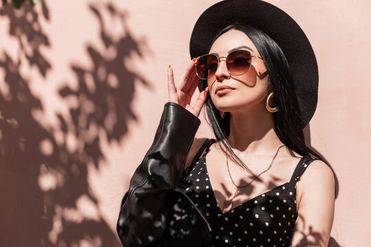 Glamorous young brunette woman in beautiful fashionable black clothes straightens sunglasses outdoors. Lovely sexy girl in dress in leather jacket in hat posing and enjoys sunlight. Summer fashion.