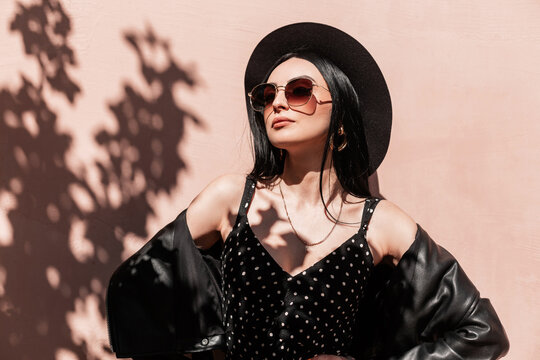 Beauty portrait young woman in stylish hat in fashion dress in leather vintage jacket in sunglasses on background pink wall on sunny day. Gorgeous girl in elegant summer wear enjoys sunlight on street