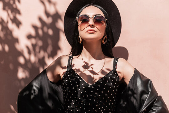 Portrait pretty young chic woman in elegant hat in fashion dress in leather vintage jacket in sunglasses on background pink wall on sunny beach. Attractive girl in summer clothes enjoy mood