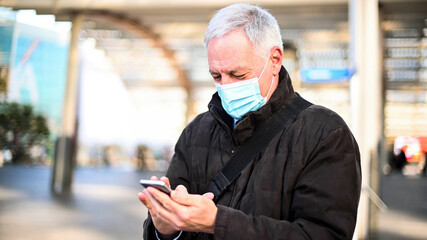 Senior man using his smartphone outdoor while wearing a mask to protect from Coronavirus pandemic