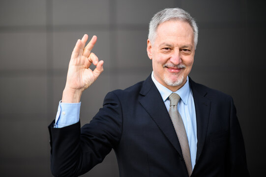 Mature business man portrait outdoor making the Okay sign with his hand