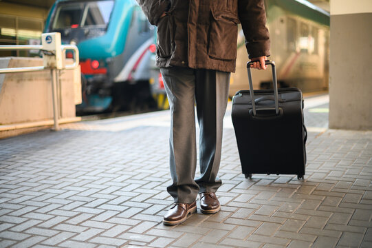 detail of a traveller walking in a train station with his trolley