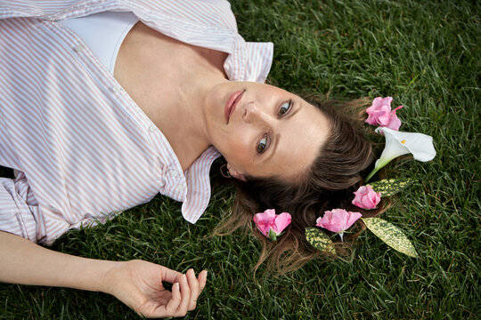 A portrait of a beautiful young woman with short hair lies on the green grass in spring. Light striped shirt.