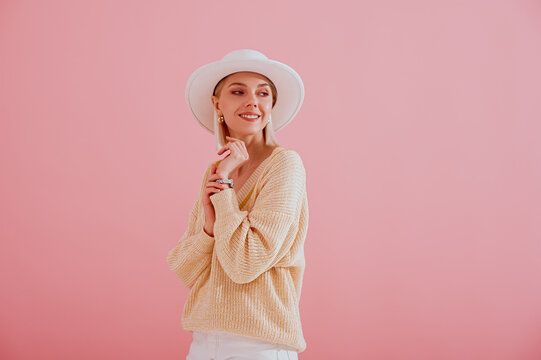 Happy smiling woman wearing trendy yellow sweater, white hat posing on pink background. Spring fashion conception. Copy, empty space for text