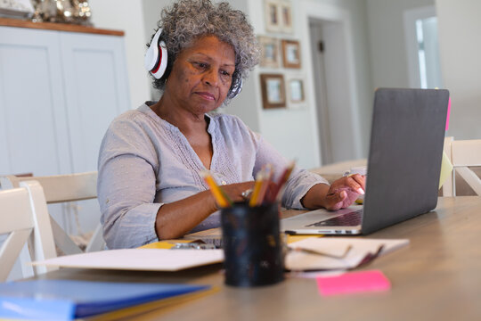 Thoughtful african american senior woman wearing headphones using laptop at home